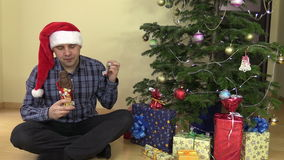 Man with red hat eat Santa form chocolate with satisfaction. Man with red hat eat delicious Santa form chocolate with satisfaction. Decorated Christmas tree with stock video footage