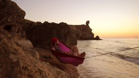 Man in red hat in a hammock on a sandy beach enjoing amazing golden sunset view. 1920x1080 stock footage