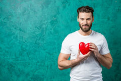 Man with red heart. Handsome man in the white t-shirt holding red heart on the painted green wall background. Valentine`s Day concept Royalty Free Stock Photos