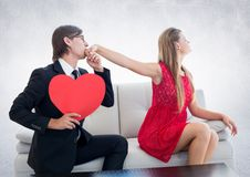 Man with red heart pleasing upset woman. At home Stock Images