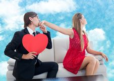 Man with red heart pleasing upset women. Against digitally generated sky background Stock Photos