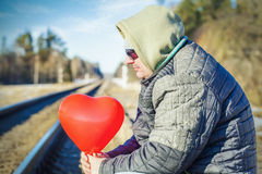 Man with red heart-shaped balloon near railway Royalty Free Stock Images