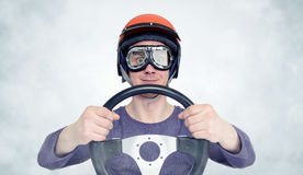 Man in red helmet and goggles with steering wheel. car driver concept Stock Image