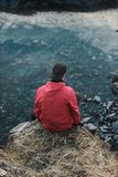 Man in Red Hoodie Sitting on Cliff Stock Photography