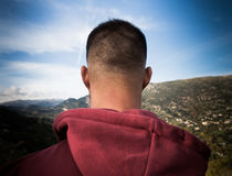 Man in Red Hoodie Standing on Mountain Under Blue and White Sunny Cloudy Sky Stock Photos