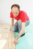 Man in red installing flooring Royalty Free Stock Photography
