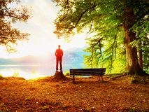 Man in red jacket and black trousers stand on tree stump. Empty wooden bench at mountain lake. royalty free stock photos