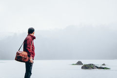 Man in Red Jacket Carrying Brown Leather Shoulder Bag Standing on Foggy Weathered Field Stock Photography