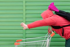 A man in a red jacket with a hood on his head and a backpack on his back with a colored package quickly rolls the cart from the stock photos