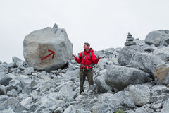 Man in red jacket lost on obvious trail. The trail is marked with two large cairns and a giant red arrow painted on a boulder, but this man appears to be lost Stock Photos