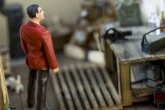Man with a red jacket standing in a model garage. Looking at tools, with blurry background Stock Photography