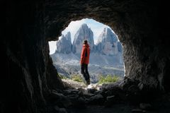 Man in Red Jacket Standing Outside of Cave in Front of Three Mountains Stock Photo
