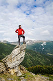 Tourist in mountains. Man in red jacket standing on a rock. There is a beautiful mountain landscape around. The sky is cloudy Royalty Free Stock Images