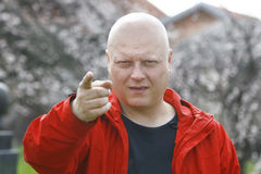 Man In A Red Jacket Threatening With Finger And Alerts Stock Images
