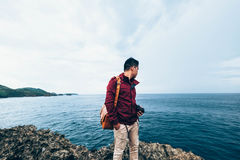 Man in Red Jacket Wearing Orange Messenger Bag Leaning on Calm Sea Stock Photo