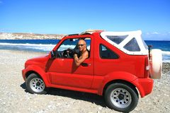Man with red jeep. Man with a red jeep on a Greek shore Royalty Free Stock Photo