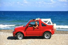 Man with red jeep. Man with a red jeep on a Greek shore Royalty Free Stock Photos