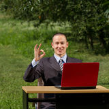 Man with red laptop working outdoors Stock Photography