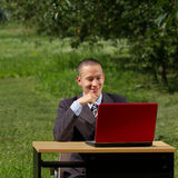 Man with red laptop working outdoors Stock Photo