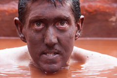 Man from the red mud. Close up of a man submerged in the red mud bath with his face completely covered in mud Royalty Free Stock Image