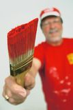 Man with red paintbrush. A senior man holding out a brush with red paint Stock Image