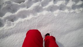 Man with red pants walks on the snow. In the mountains stock footage