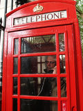 Man in a red phone booth, London Stock Images