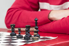 Man in red playing chess in old chessboard Stock Images