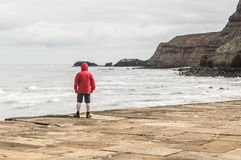 Man in red rain jacket cagoule on Whitby Harbour Stock Images