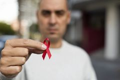 Man with red ribbon for the fight against AIDS royalty free stock images