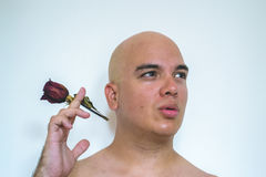 A man with a red rose. Closeup of a man simulating smoke a red rose Royalty Free Stock Images