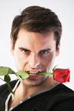 Man with a red rose in his mouth Stock Photography