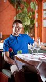 The man with red rose  in restaurant Stock Photo