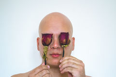 A man with red roses on his eyes. Closeup of a man with old red roses covering his eyes, and  with a white background Stock Photos