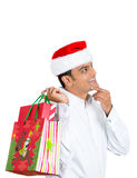 Man in red santa claus hat holding shopping bag over shoulder Royalty Free Stock Photo