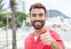 Man with red shirt and beard in the city showing thumb Stock Photography