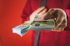 A man in a red shirt with a card holds in his hand a wad of bills on a red background. Business money cash dollar rich fashion person paper businessman currency stock image