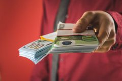 a man in a red shirt with a card holds in his hand a wad of bills on a red background stock photography
