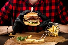 A man in a red shirt eating a burger.  Stock Photography
