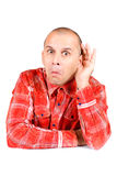 Man in red shirt with hand on his ear Stock Image