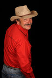 Man in red shirt and hat. A studio portrait of a man wearing red shirt and cowboy hat looking back over shoulder.  Model looks like Burt Reynolds.  Black Royalty Free Stock Photos