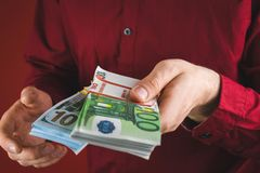 man in red shirt holding bundles of money on red background stock photo
