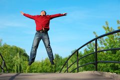Man in red shirt jumps outdoor on bridge Royalty Free Stock Photo