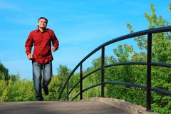 Man in red shirt  runs on bridge in summer Royalty Free Stock Photography