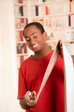 Man in red shirt stretching out bandage preparing wrist support on right hand posing for camera, blurry bookshelves Stock Images