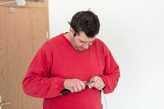 Man in red shirt stripping wire. Man worker in red shirt stripping wire with cutting knife standing indoors Stock Photography