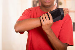 Man in red shirt wearing black wrist brace support on right hand and gripping arm with other Royalty Free Stock Photo