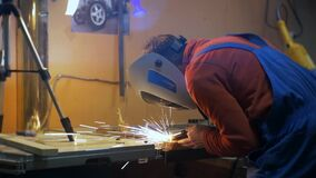 Man in a red shirt and wearing a protective mask conducts welding work. Sparks are flying stock footage