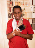 Man in red shirt wearing wrist brace support on right hand posing for camera, holding his arm simulating painful Royalty Free Stock Photos