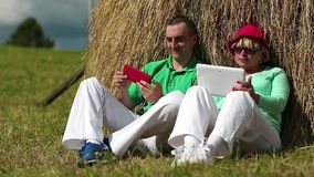 Man with red smartphone and woman with Tablet-PC sits near a haystack stock video
